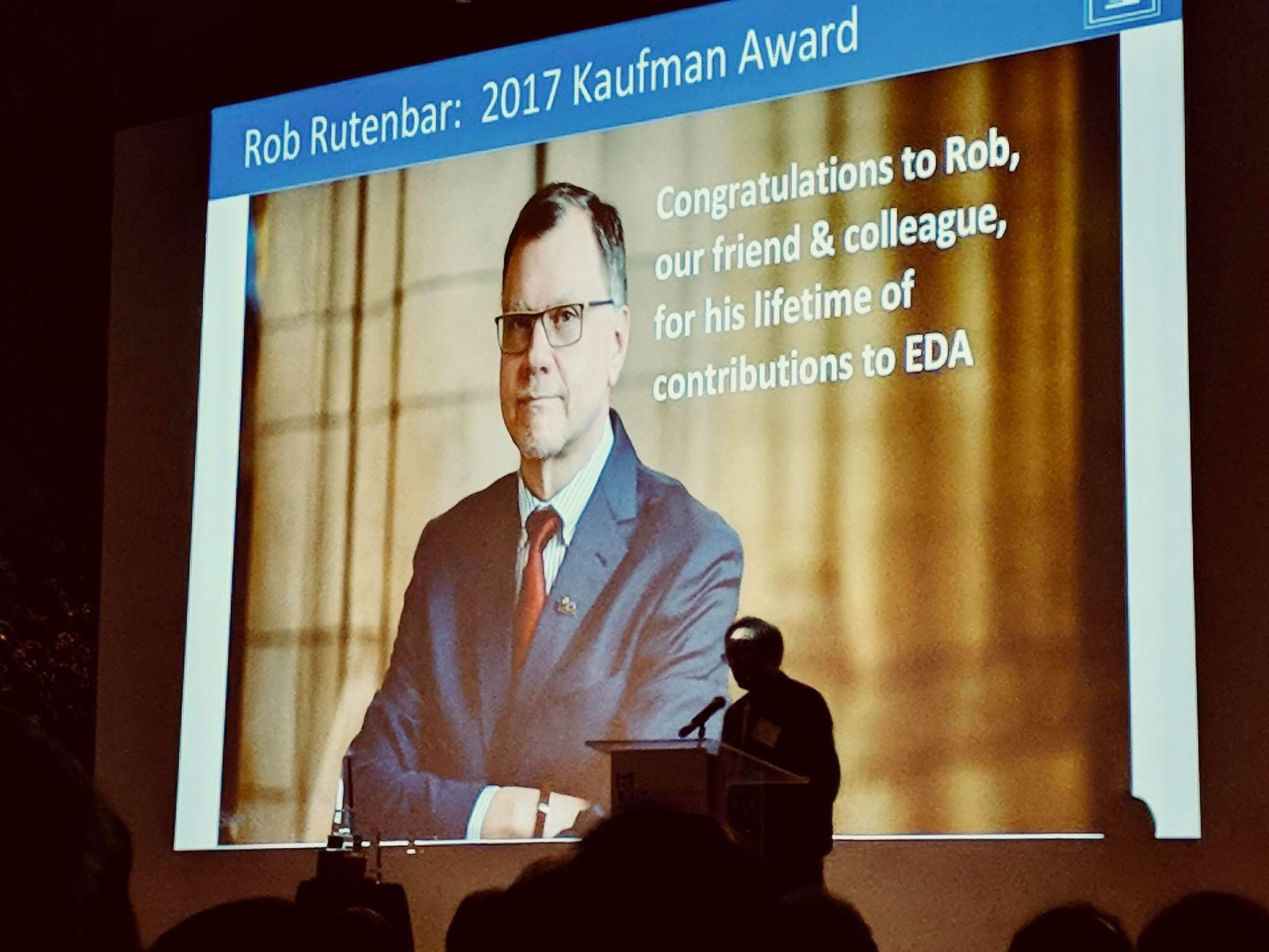 "Photo of the Kaufman EDA Award ceremony, 2018. The photo shows a projector screen with an image of Rutenbar and the words, ""Congratulations to Rob, our friend and colleague, for his lifetime of contributions to EDA""."